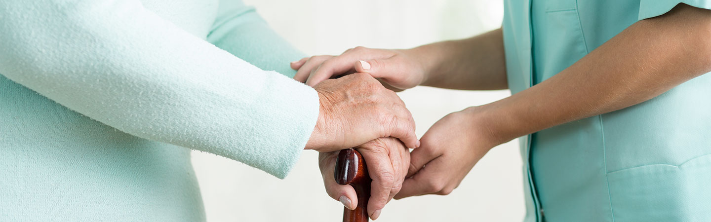 Close up of caregiver holding hand of elderly person with cane.