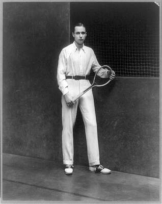 Old-fashioned photo of man holding tennis racket.