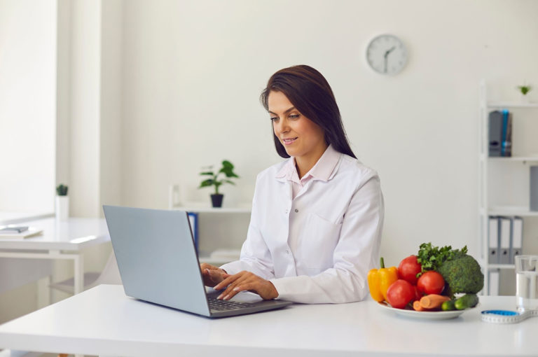 female wellness coach at laptop computer